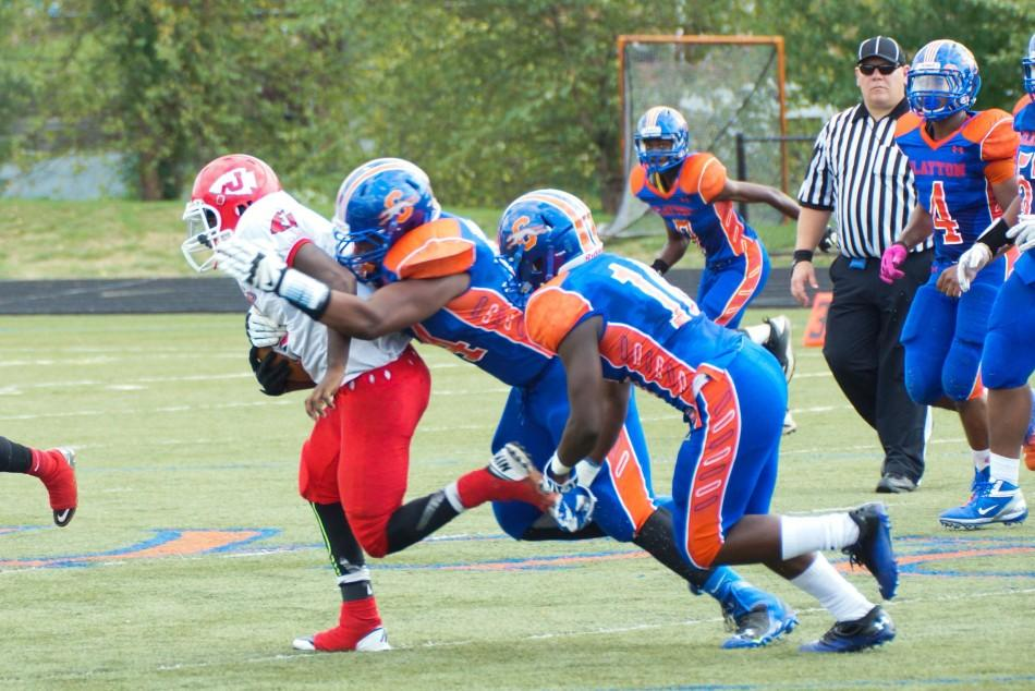 Two members of the varsity Clayton football team tackle a member of the opposing team. Football players experience more concussions than all other groups of student athletes (Alessandra Silva).