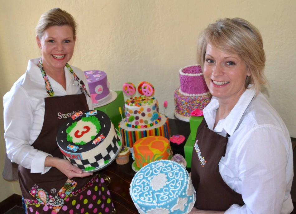 The two co-founders of Sweetology, Kara Newmark (left) and DeAnn Bingaman (right) stand with their decorated cakes.
