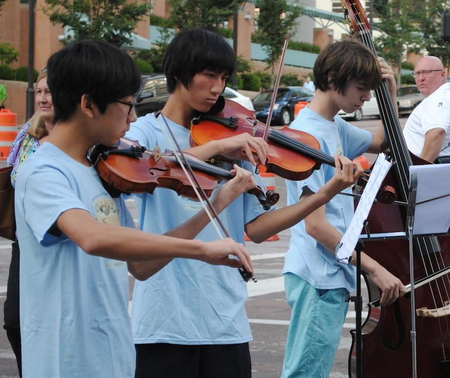 Lawrence Hu, Matthew DelaPaz, and Benjamin Schneider playing their instruments at the Art Fair.