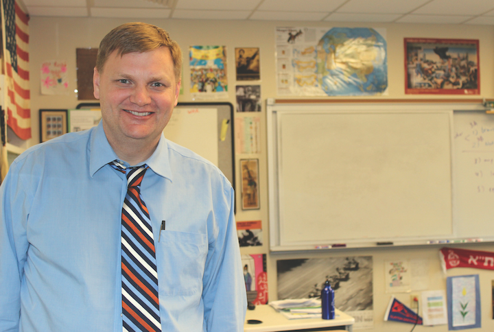 Paul Hoelscher stands in his history Classroom. Hoelscher is a history teacher at CHS and the social studies coordinator for the district (Photo by Gwyneth Henke).