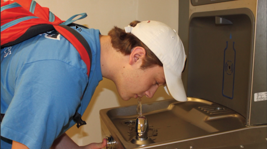 Senior Max Steinbaum drinks from a water fountain at Clayton High School. (Photo by Erin Castellano)