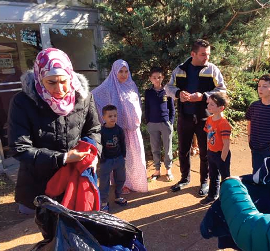 Syrian Refugees receiving coats from a coat drive in st. Louis