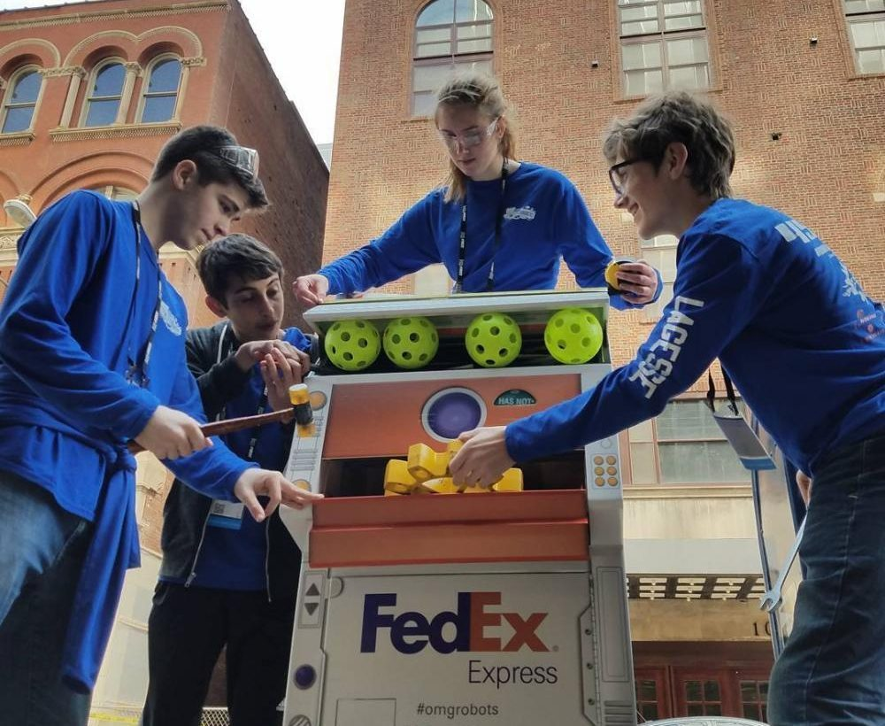 Robohounds pose with a robot-themed drop box for the Fedex Innovation Challenge. From left to right: Zachary Sorensen, Justin Guilak, Echo Gaugush, Jacob LaGesse.