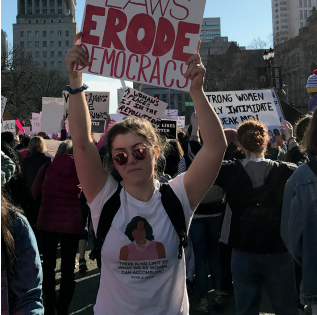 Photo of Oyster at the St. Louis Women's March holding a sign reading,