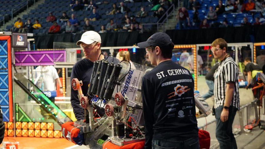 CHS engineering teacher Stephen Beauchamp (left) and Owen St. Germain, Class of 2018 (right) carry their team's robot off the field at a FIRST robotic competition in 2018.