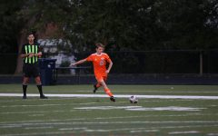 Senior Greg Pierson passes the ball to a teammate at a boys' varsity soccer game.