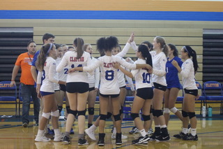 The volleyball team talking during a time out.