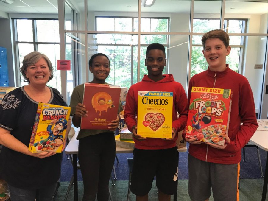 Michelle Schiller-Baker (left) and students hold boxes of cereal. They were helping provide breakfast for St. Martha's Hall.