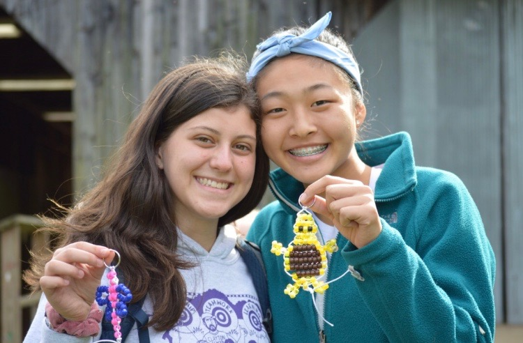 Counselors%2C+Abby+Mann+and+Kim+Cheng+hold+up+the+beads+animals+that+they+made.