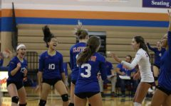 The girls' varsity volleyball team celebrates after scoring a point in their game on Oct. 3.