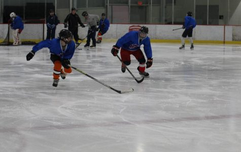 Two Clayton ice hockey players race against each other across the ice during one of the team's practices.