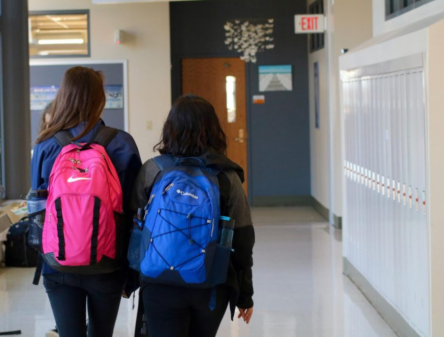 Two+CHS+students+walk+down+the+hall+together+with+their+backpacks+on.+Ingrid+and+Sophie+discuss+the+physical+strain+backpacks+have+on+high+school%2C+and+discuss+solutions+to+this+problem.