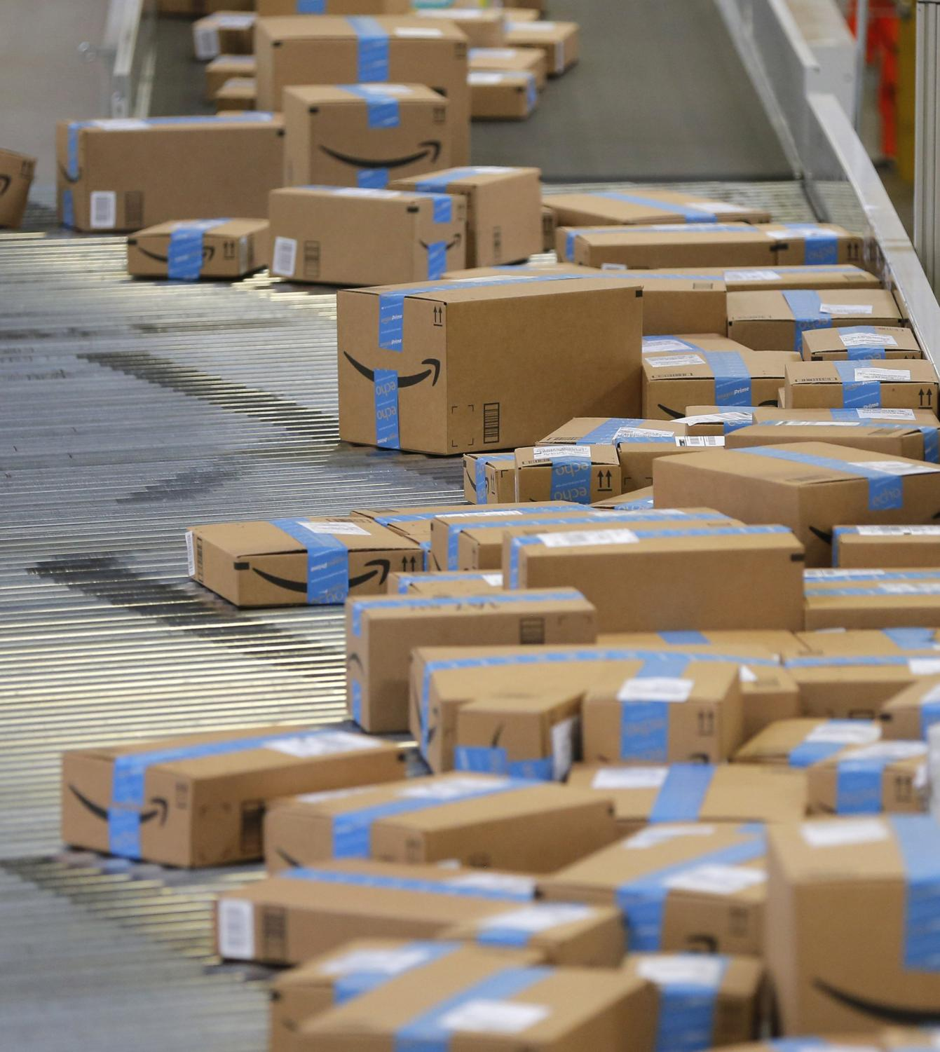 Packed and sealed boxes move toward the trucks as employees fill orders at Amazon Fulfillment Center in Haslet, Texas on Monday, Nov. 28, 2017.