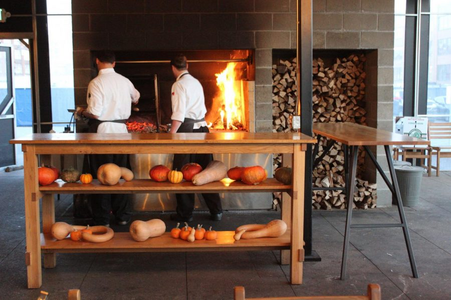 Vicia staff cook food over a pile of hot coals and an open fire in the restaurant's main area.