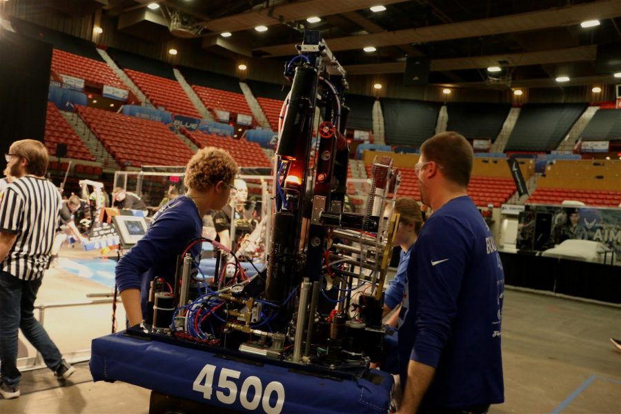 The Robohounds carry their bot towards the competition field before a match in Oklahoma City. From left to right: junior Max Walter-Morrissey, sophomore Olivia Zindel, engineering teacher Stephen Beauchamp.