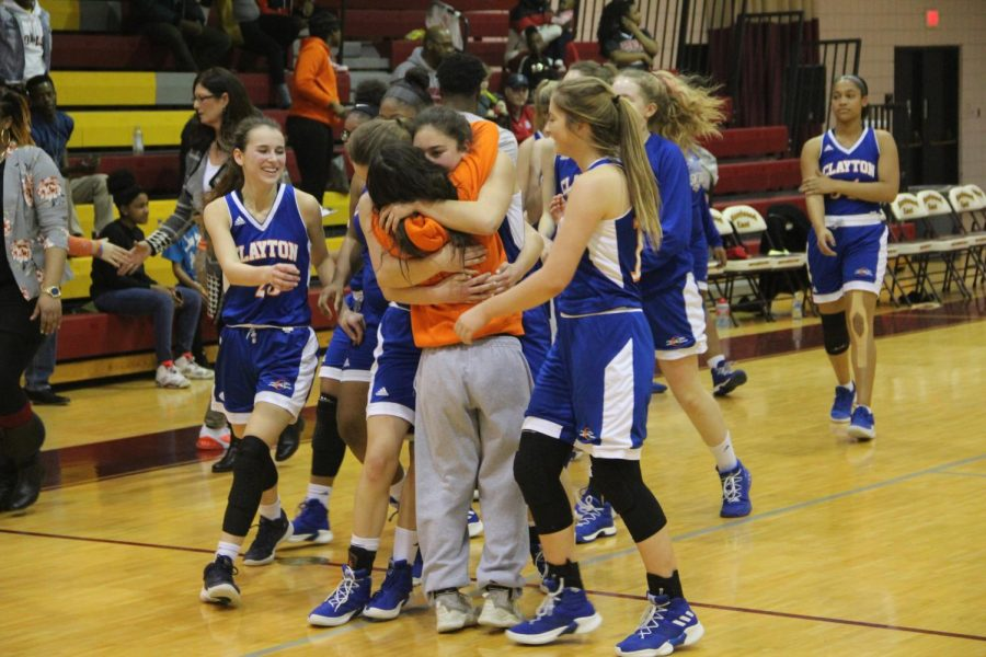 Juniors Sammy Williams (left) and Sara Litteken share a celebratory hug as the rest of their teammates run up to join in, after beating Jennings 38-26 in the Class 4 District 6 Championship Finals.