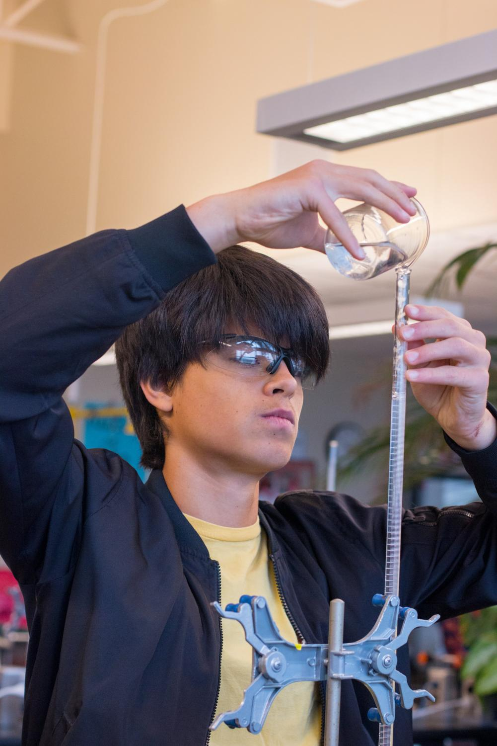 Junior Emilio Rosas-Linhard pours a solution into a graduated cylinder during a chemistry class. Even though the official measurement system is imperial, American scientists almost exclusively teach and use the metric system.