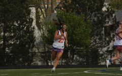 Caroline Marsden runs across the field during a lacrosse game.