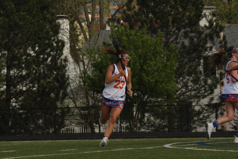 Caroline Marsden runs across the field during a lacrosse game.