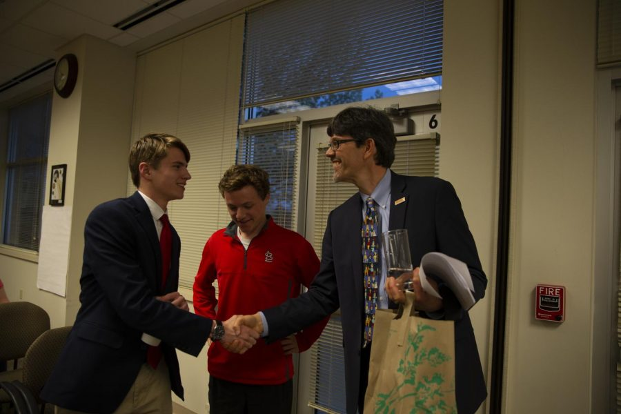 Greg Pierson shakes hands with new board president Joe Miller after a successful 6-1 vote to approve the Student Representation on the Board of Education.