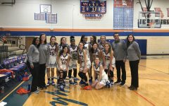 The Girls' Varsity Basketball team poses for a photo with their victory plaque.