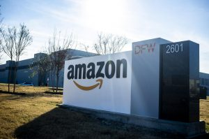 The prominent Amazon company logo is displayed on the entrance to a fulfillment center in Grapevine, Texas.