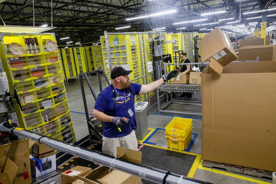 Salvador Ribaul throws a box away at an Amazon fulfillment center in Grapevine, Texas on December 5, 2018.