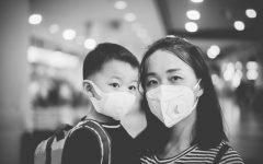An Asian mother and a kid wearing masks in the picture.