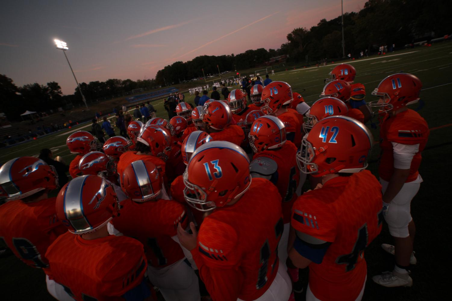 Football players huddle before a game at Clayton High School