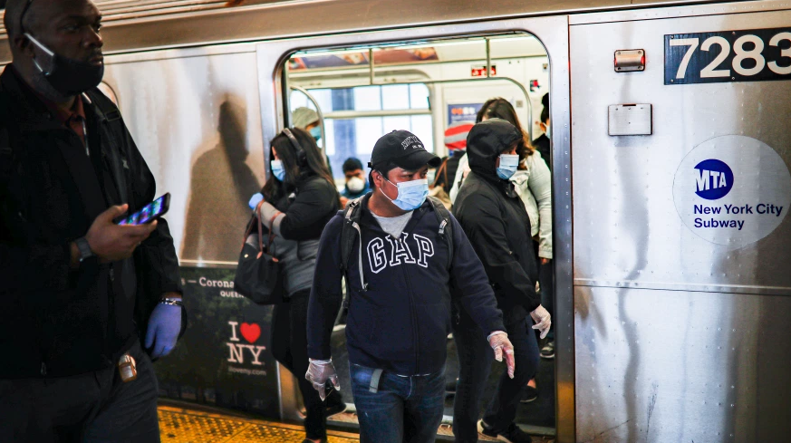 Subway riders exit the train in New York City while wearing masks due to the coronavirus pandemic.  When not wearing a mask, you could get mild symptoms if you combat the virus through viral spread.