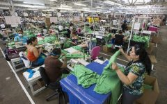 Garment workers sewing t-shirts on the warehouse floor at Los Angeles Apparel on August 4, 2017, in Los Angeles.